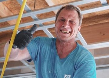 Mitarbeiter für den Innenausbau lacht während der Arbeit.