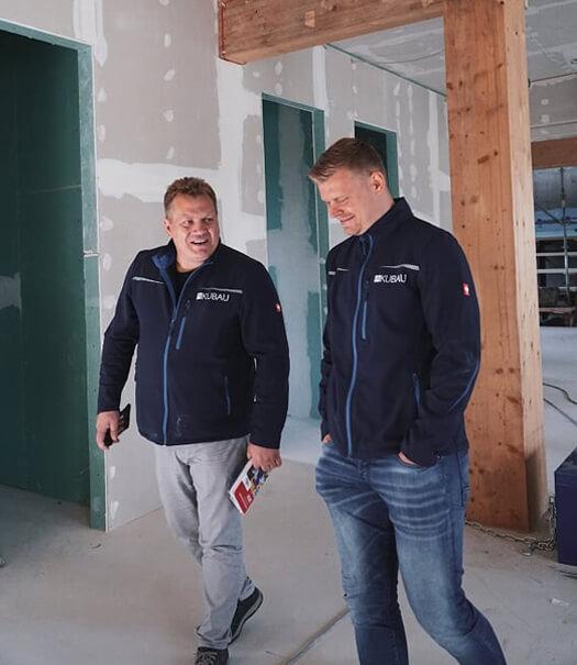 Zwei Mitarbeiter der Kubau GmbH auf einer Baustelle.
