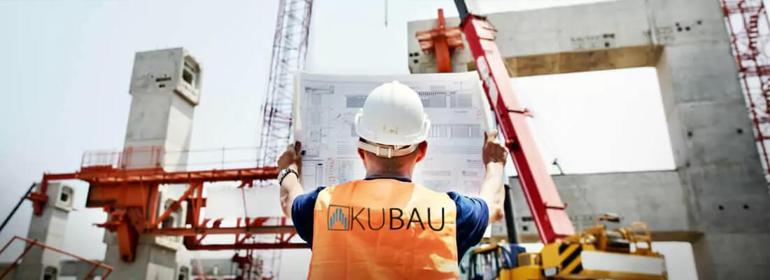 Mitarbeiter eines Bauunternehmens haelt einen Bauplan hoch.