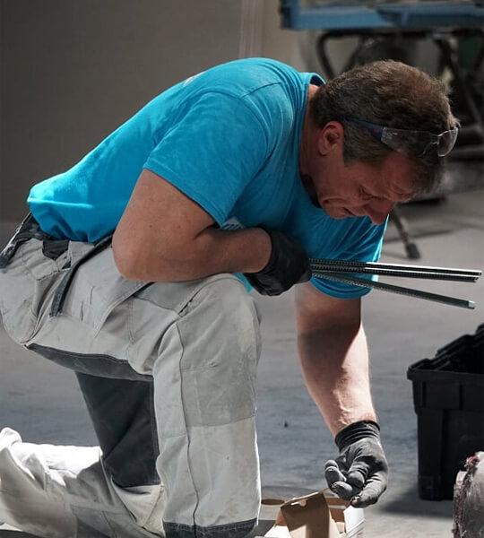 Mitarbeiter des Bauunternehmens sammelt Werkzeug und Schrauben ein.