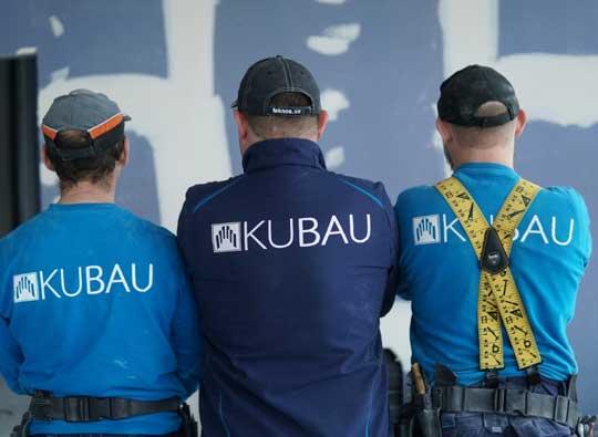 Drei Trockenbaumitarbeiter mit dem Rücken auf einer Baustelle